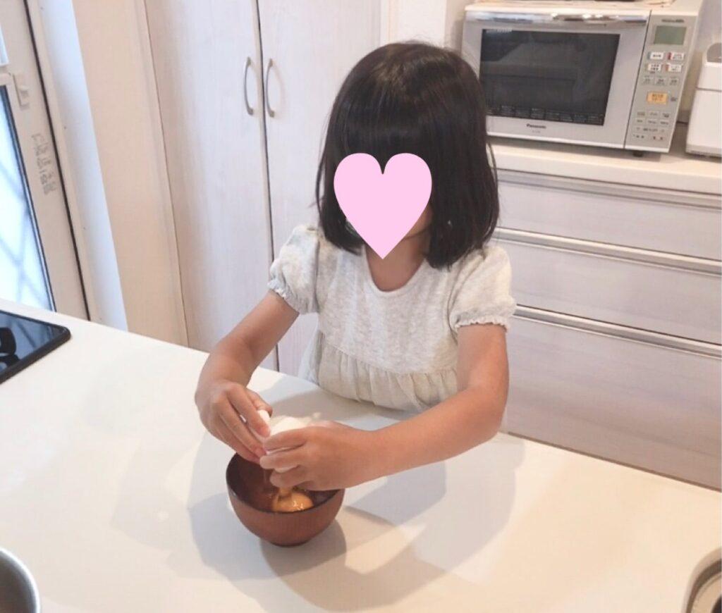 卵を割る5歳の娘